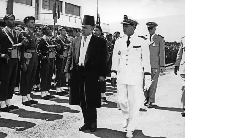 الرئيس التونسي الحبيب بورقيبه مع وزلي العهد المغربي مولاي حسن يستعرض حرس الشرف خلال زيارته للرباط 1957