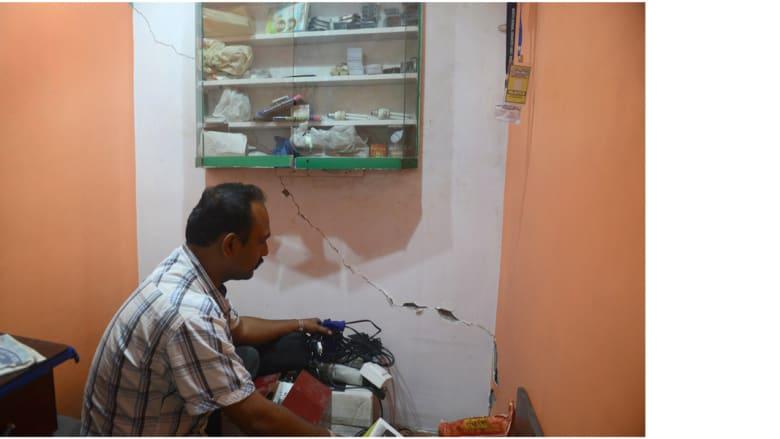 بائع هندي في دكان تظهر الشروخ في جدرانه بعد الزلزال سيليغوري، الهند 25 أبريل/ نيسان 2015