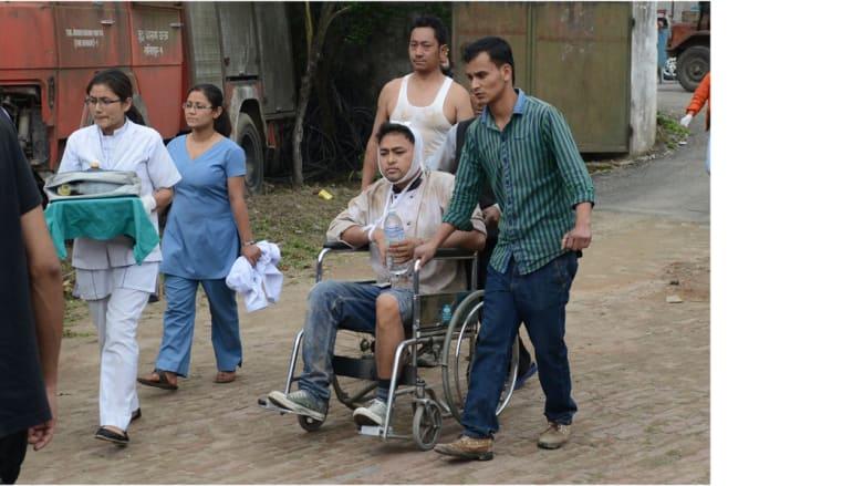 مواطنون نيباليون في لاليتبور يدفعون أحد المصابين على كرسي متحرك، 25 أبريل/ نيسان 2015