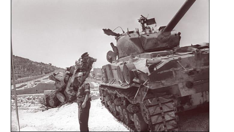 ناقلة جنود معطوبة وتقف قربها دبابة إسرائيلة على الطريق بين بيت لحم والقدس، بعد الحرب عام 1967