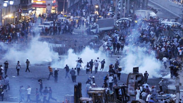 محتجون مناهضون للحكومية يهربون من خراطيم المياه والغاز المسيل للدموع على ساحة تقسيم في اسطنبول يوم 22 يونيو 2013.