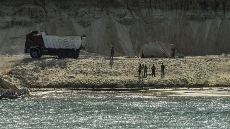 عمال مصريون يعملون على ضفاف المجرى المائي الجديد لقناة السويس