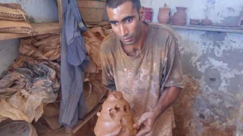 حرفي يحمل الطين بعد عجنه