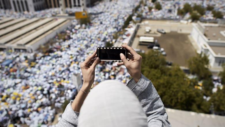 سيدة تلتقط صورة أثناء أداء الحجيج للصلاة في مسجد نمرة