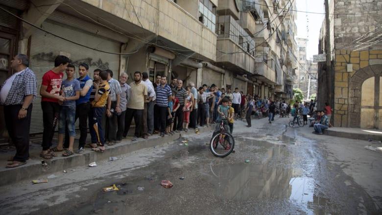 سوريون يقفون في الصف بانتظار شراء الخبز في حي بشمال مدينة حلب