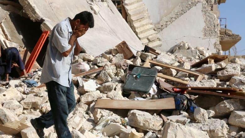 رجل سوري يبحث عن ضحايا تحت أنقاض مبنى منهار بعد غارة جوية في صاخور بمدينة حلب