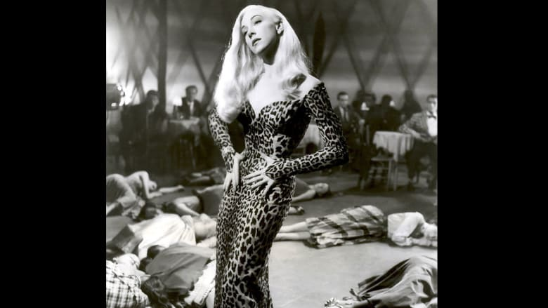 الممثلة والمتزلجة المحترفة بيليتا ترتدي فستاناً بطبعة جلد الفهد في العام 1956.