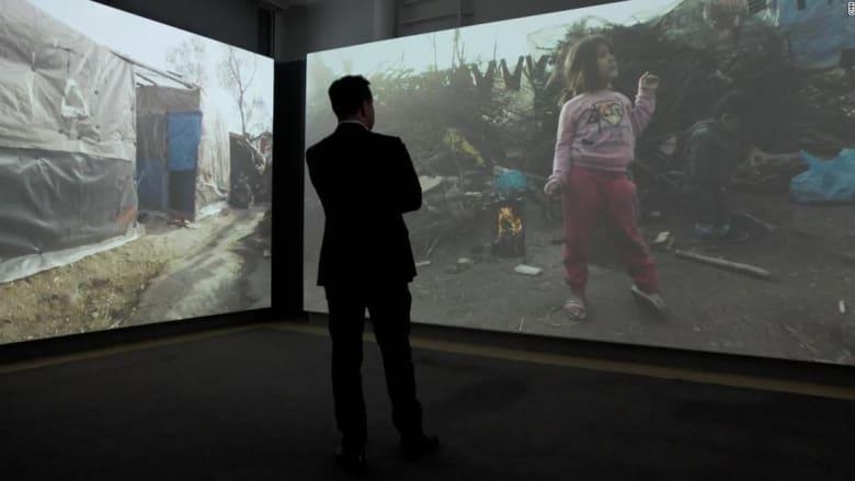 """شاهد.. """"آلة الزمن"""" داخل معرض تجعلك تسير في مخيم موريا للاجئين قبل الكارثة"""