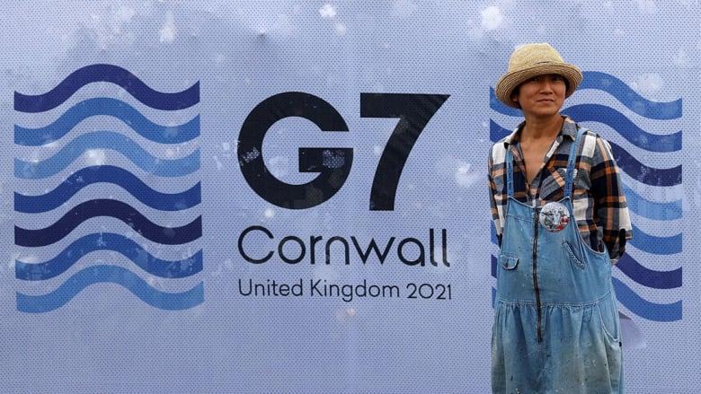 أحد المارة يقف بجانب شعار G7 في بريطانيا 2021