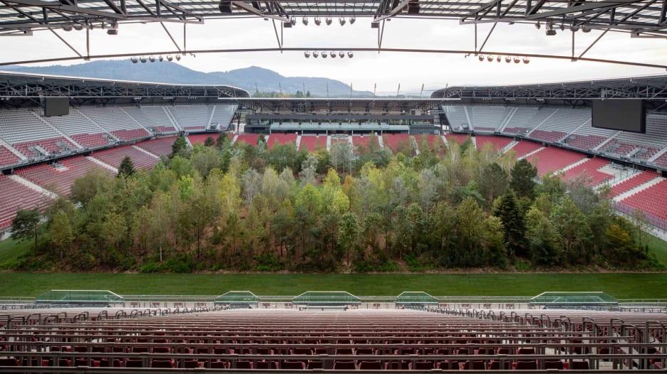 شخص يزرع غابة وسط ملعب كرة قدم