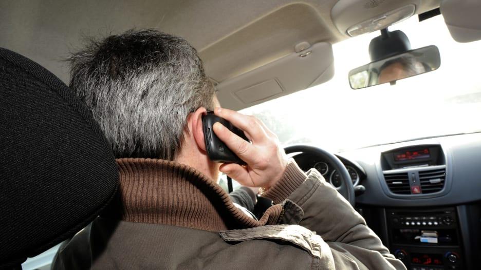 صورة لشخص يستخدم الهاتف أثناء قيادة مركبة