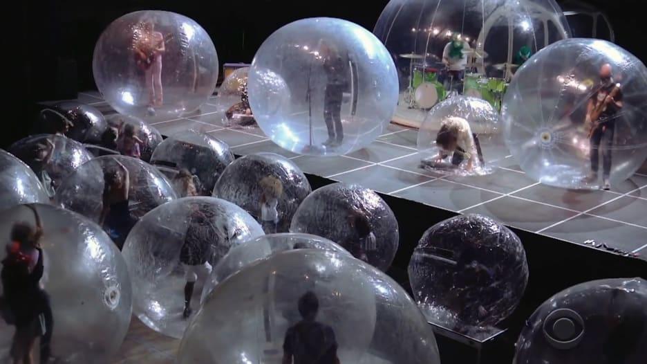فرقة تؤدي حفلاً موسيقياً أمام جمهورها وجميعهم داخل فقاعات بلاستيكية