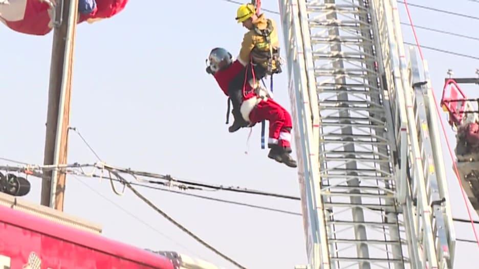 بابا نويل عالق فوق عمود كهرباء وأفراد الإنقاذ يهرعون له.. ماذا حدث؟