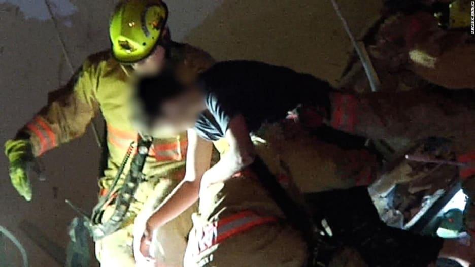 شاهد لحظة إخراج طفل على قيد الحياة من تحت أنقاض مبنى في فلوريدا