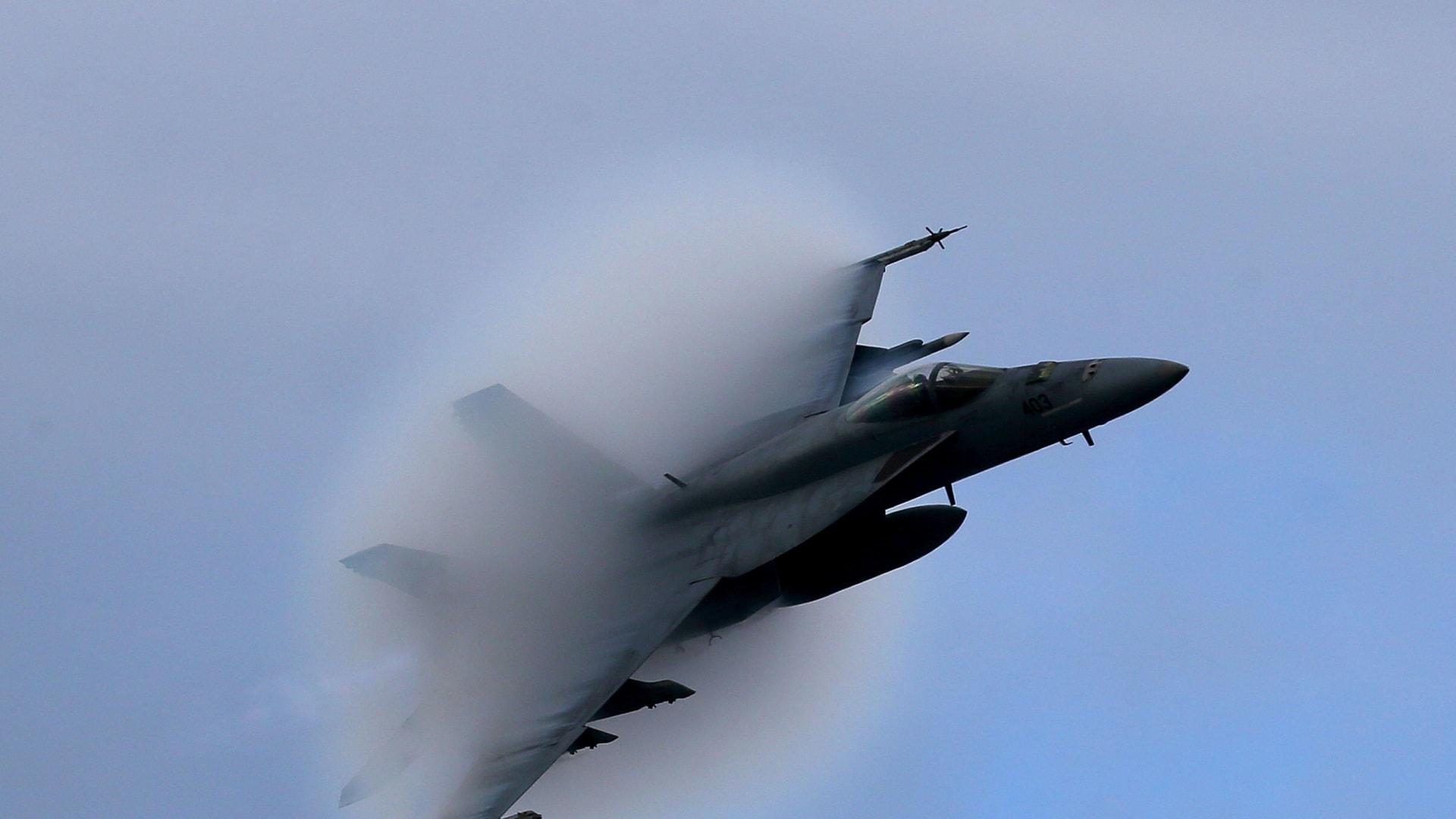 تخلق طائرة F18 Super Hornet مخروط بخار أثناء تحليقها بسرعة فوق ناقلة USS Eisenhower قبالة سواحل فيرجينيا ، 10 ديسمبر 2015