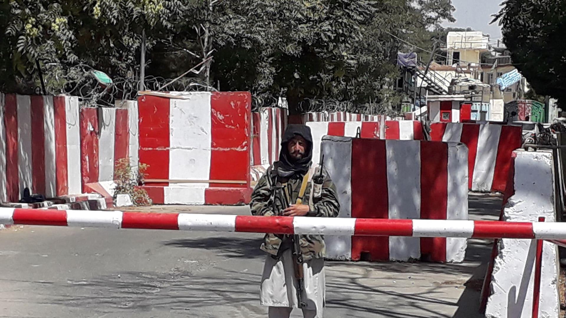 مقاتل من طالبان يقف حارسًا عند مدخل مقر الشرطة في غزنة في 12 أغسطس 2021