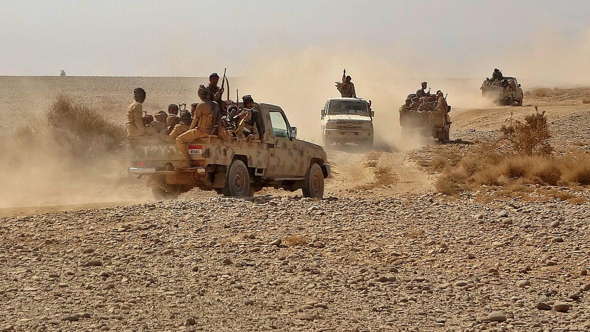 """مقاتلون يستقلون شاحنات صغيرة مع اشتباك القوات الموالية للحكومة اليمنية مع مقاتلين من الحوثيين حول قاعدة """"ماس كامب"""" العسكرية، 22 نوفمبر/ تشرين الثاني 2020"""