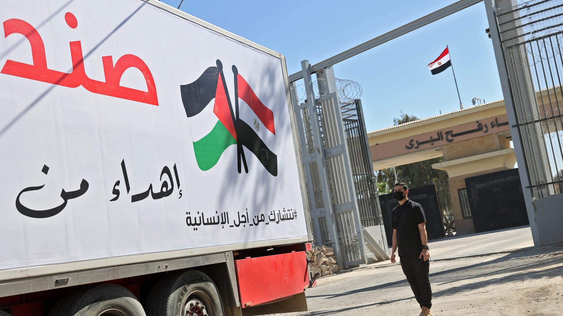 عنصر من قوات الأمن الفلسطينية يقف أمام شاحنة مساعدات مصرية وصلت إلى معبر رفح الحدودي الذي يربط قطاع غزة بمصر، في 23 مايو 2021