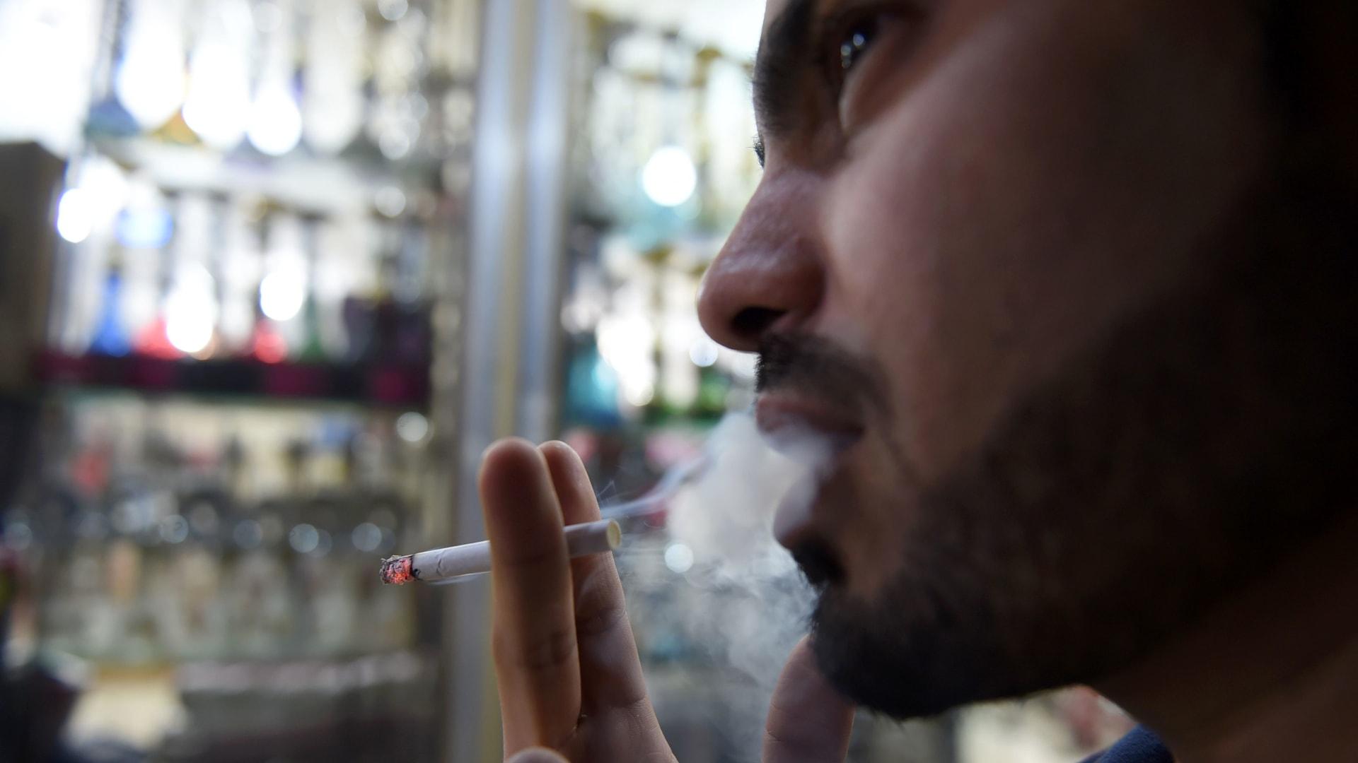 رجل يدخن خارج متجر لبيع التبغ في العاصمة السعودية الرياض في وقت متأخر من يوم 11 يونيو 2017.