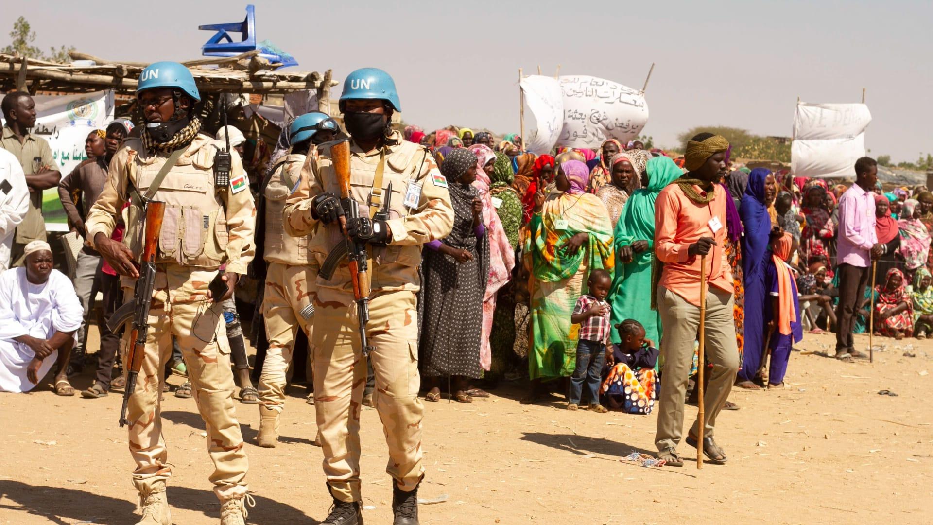 ضاء من بعثة الأمم المتحدة والاتحاد الأفريقي لحفظ السلام (يوناميد) ينظرون إلى نازحين سودانيين ينظمون اعتصامًا احتجاجًا على انتهاء ولايتهم، في مخيم كلمة بنيالا، عاصمة جنوب دارفور، في 31 ديسمبر 2020
