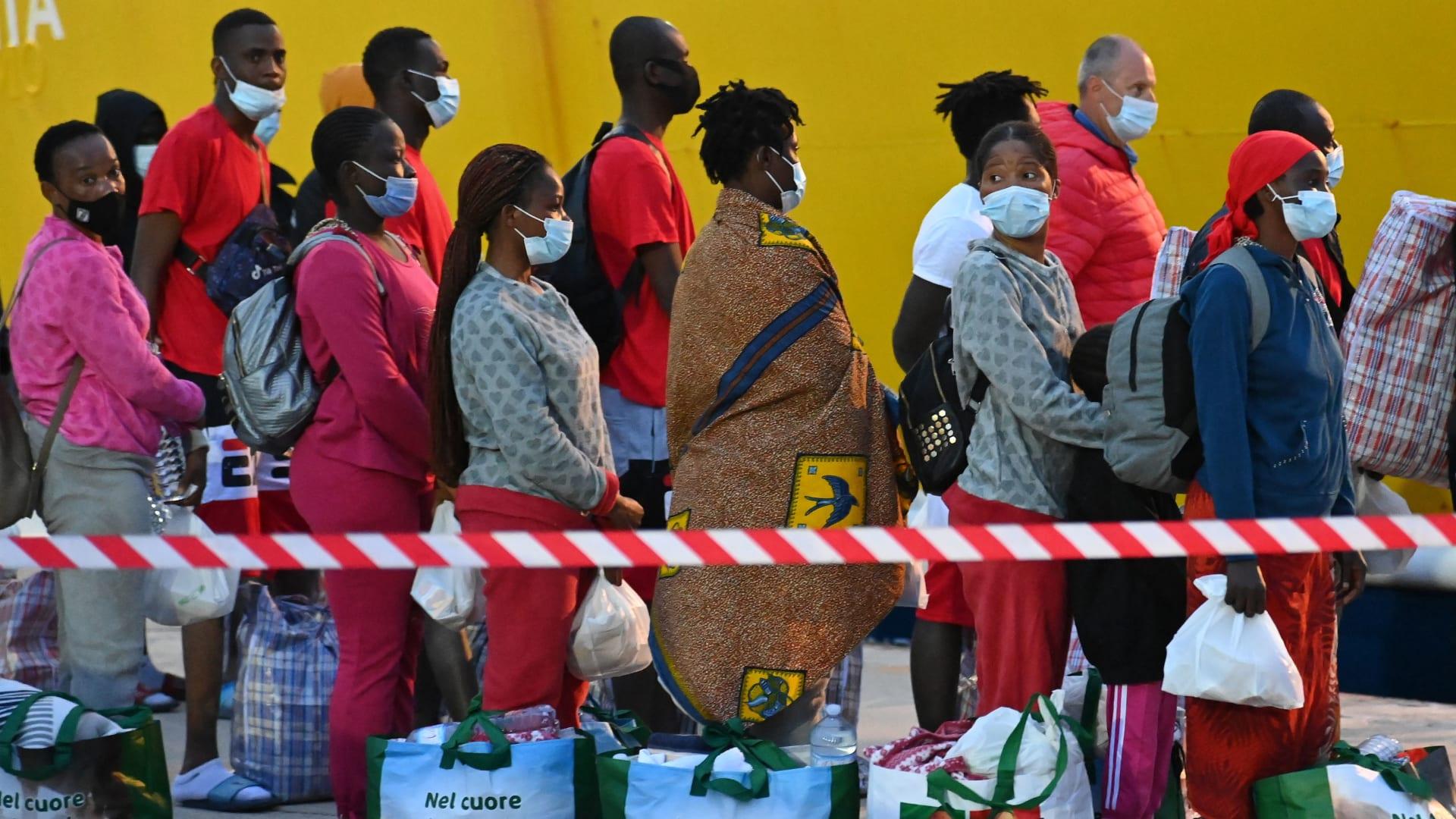 مهاجرون من مركز لإيواء المهاجرين في جزيرة لامبيدوزا الإيطالية ، يقفون في طابور يوم 14 مايو 2021