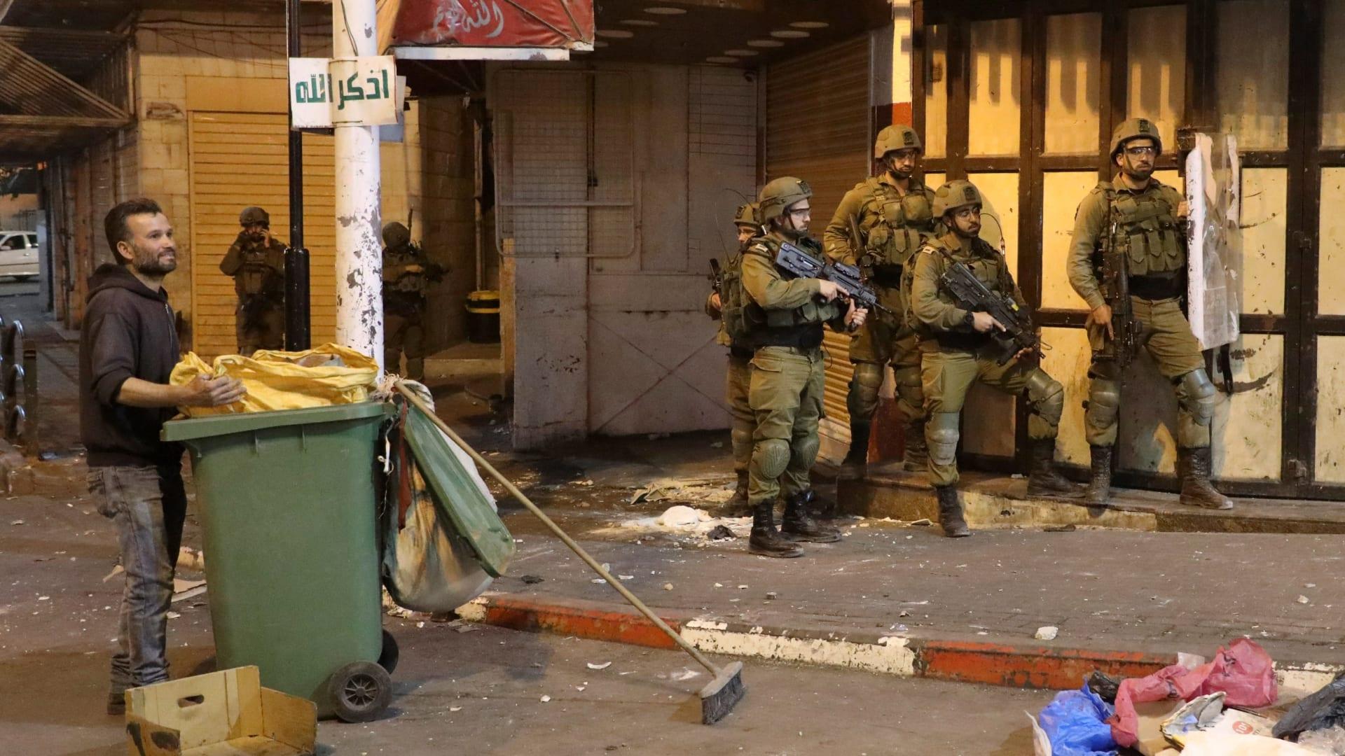 صورة تظهر عناصر أمن إسرائيلي إلى جانب عامل نظافة فلسطيني في القدس خلال المواجهات