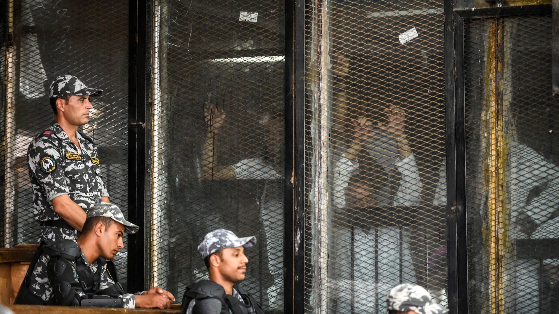 أعضاء من جماعة الإخوان المسلمين المحظورة في مصر يشاهدون داخل رصيف زجاجي أثناء محاكمتهم في العاصمة القاهرة في 28 يوليو 2018