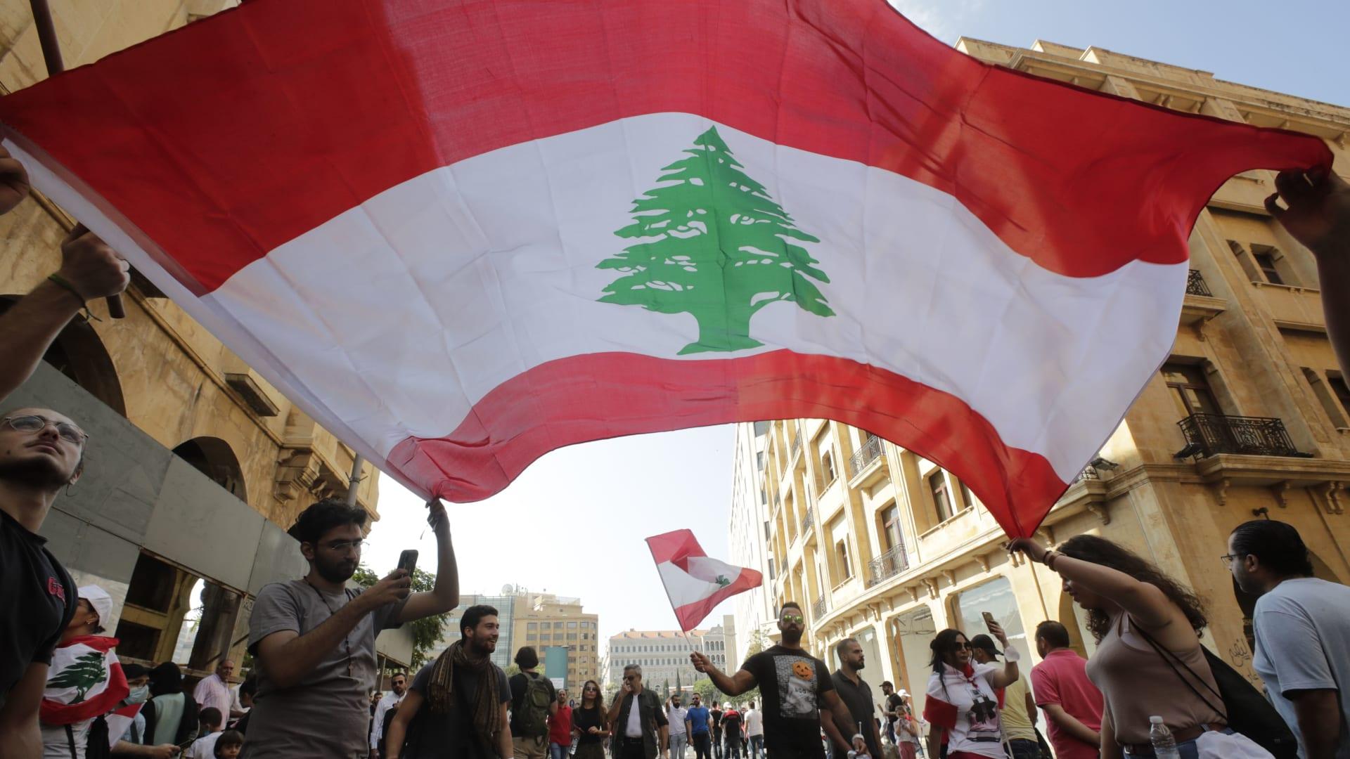 متظاهرون يلوحون بالعلم الوطني في وسط بيروت مع استمرار المئات في التجمع في 19 أكتوبر 2019 لليوم الثالث من الاحتجاجات ضد زيادة الضرائب والفساد الرسمي المزعوم بعد أن قامت قوات الأمن باعتقالات العشرات.