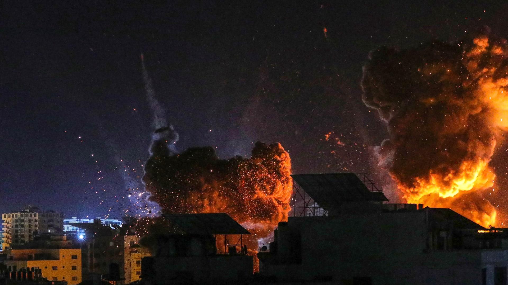 ارتفاع النار والدخان فوق المباني في مدينة غزة بعد ضربات إسرائيلية، في وقت مبكر من يوم 18 مايو 2021