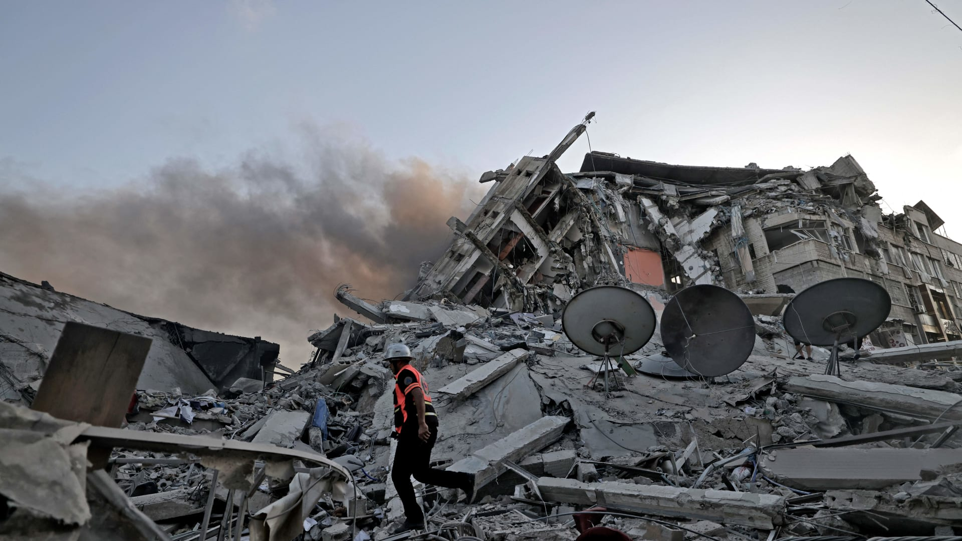 رجل إنقاذ يسير وسط أنقاض برج الشروق الذي انهار بعد تعرضه لغارة جوية إسرائيلية في مدينة غزة ، في 12 مايو 2021.