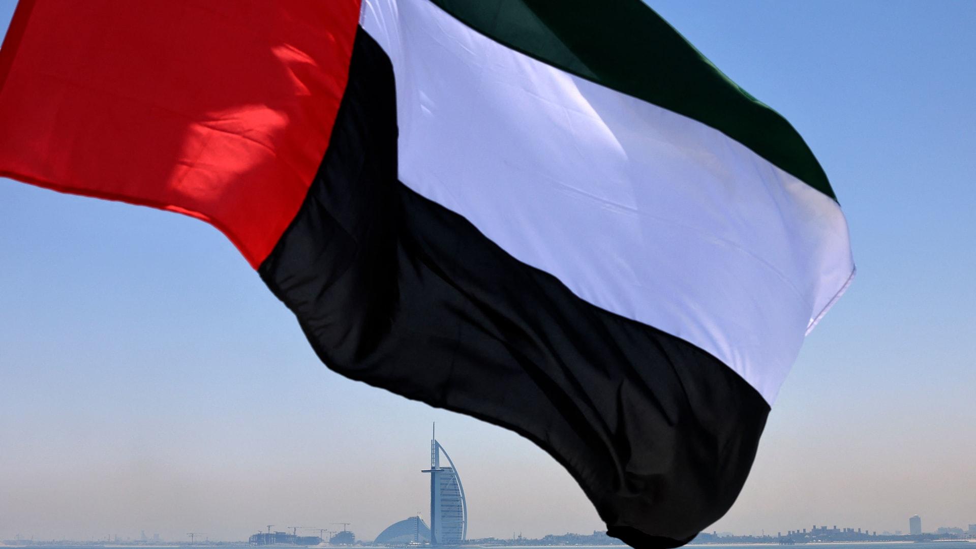 علم الإمارات يرفرف فوق مرسى دبي مع فندق برج العرب في الخلفية - في 3 يونيو 2021