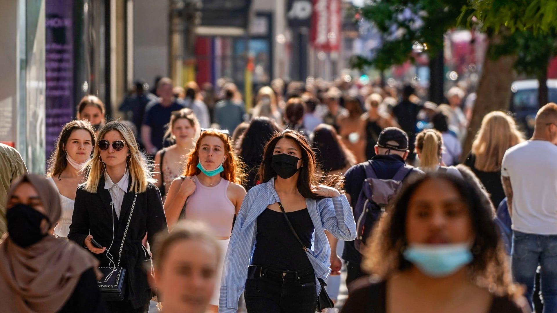 يسير المشاة، الذين يرتدي بعضهم أغطية للوجه بسبب Covid-19، أمام المحلات التجارية في شارع أكسفورد بوسط لندن في 7 يونيو 2021