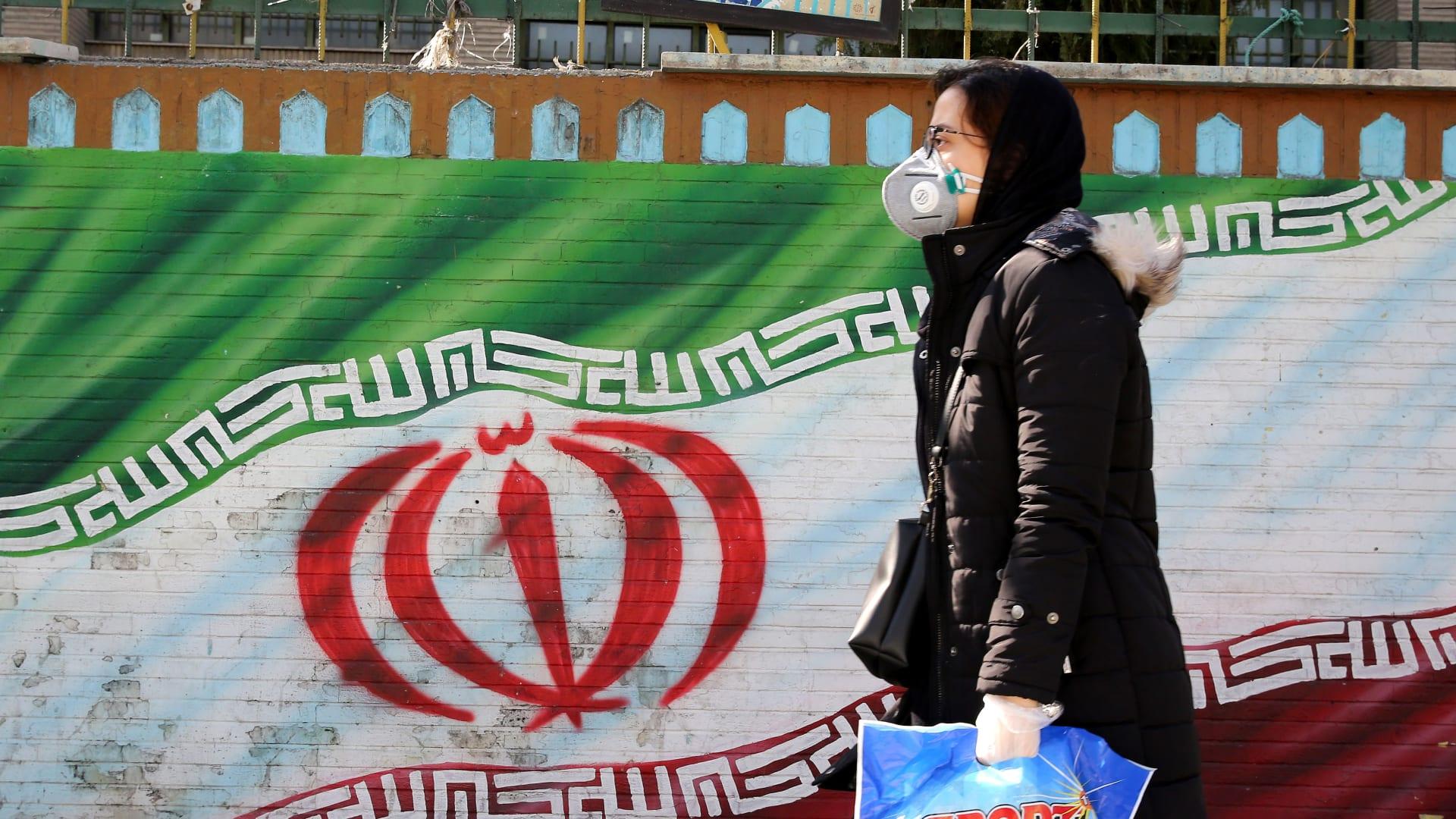 امرأة إيرانية ترتدي قناعًا تسير أمام لوحة جدارية تعرض علم بلادها في طهران، 4 مارس 2020
