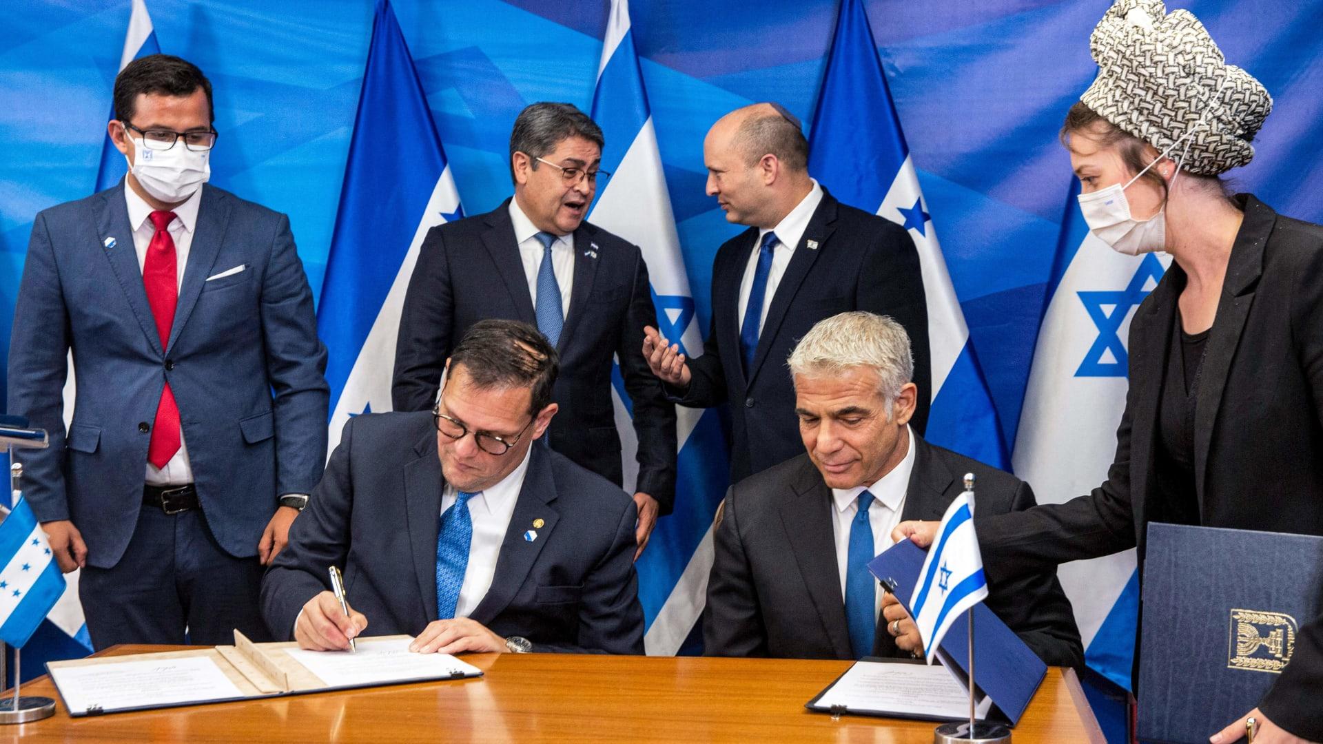 وزير الخارجية الإسرائيلي يائير لابيد (أسفل اليمين) ووزير خارجية هندوراس ليساندرو (أسفل اليسار) يوقعان اتفاقيات ثنائية في مكتب رئيس الوزراء في القدس يوم 24 يونيو 2021