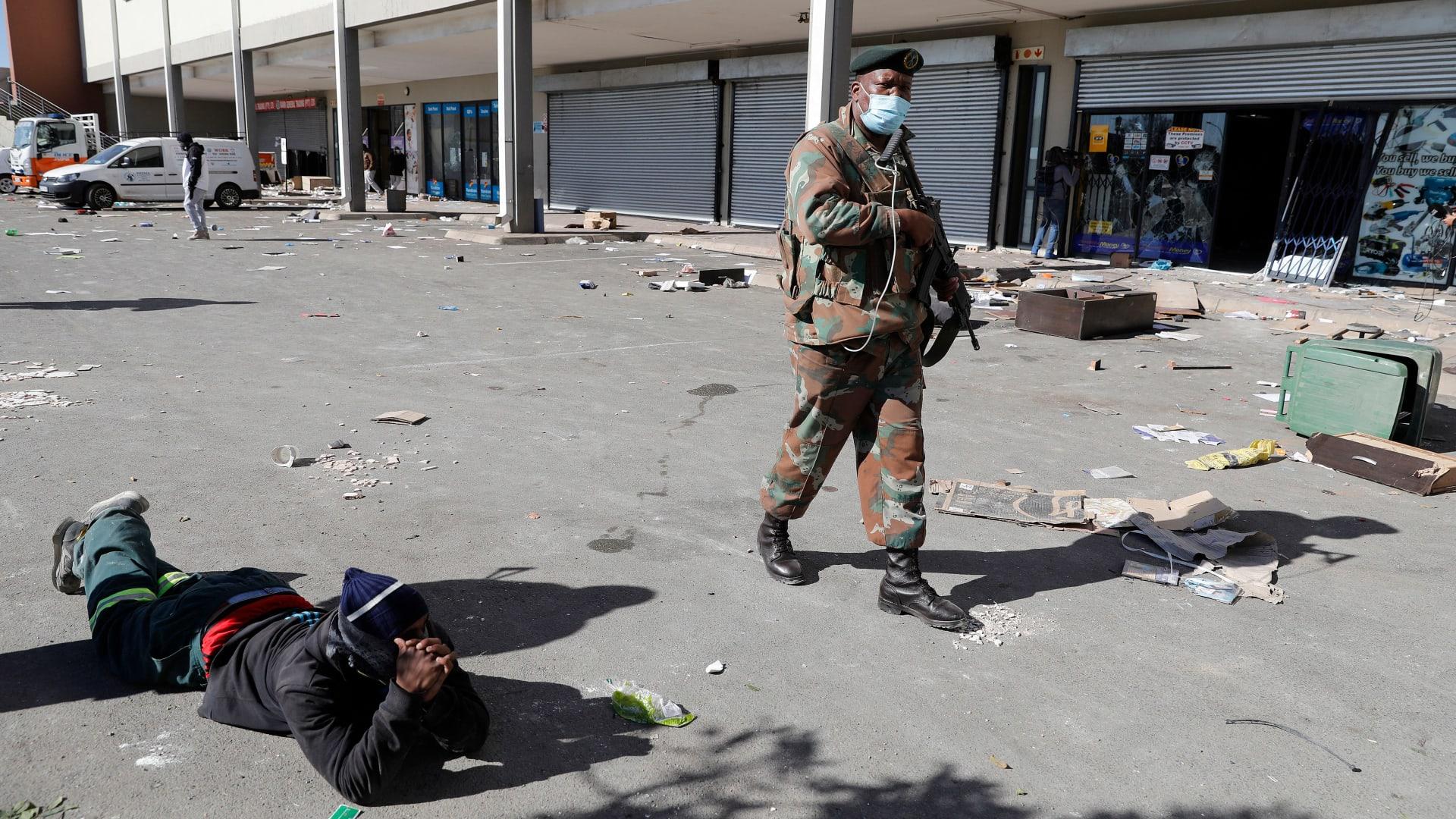 عناصر من قوات الدفاع الوطني لجنوب إفريقيا (SANDF) يقومون بدوريات في منطقة ميدان ديبلوف المنهوبة في سويتو ، جوهانسبرج في 13 يوليو 2021 ،