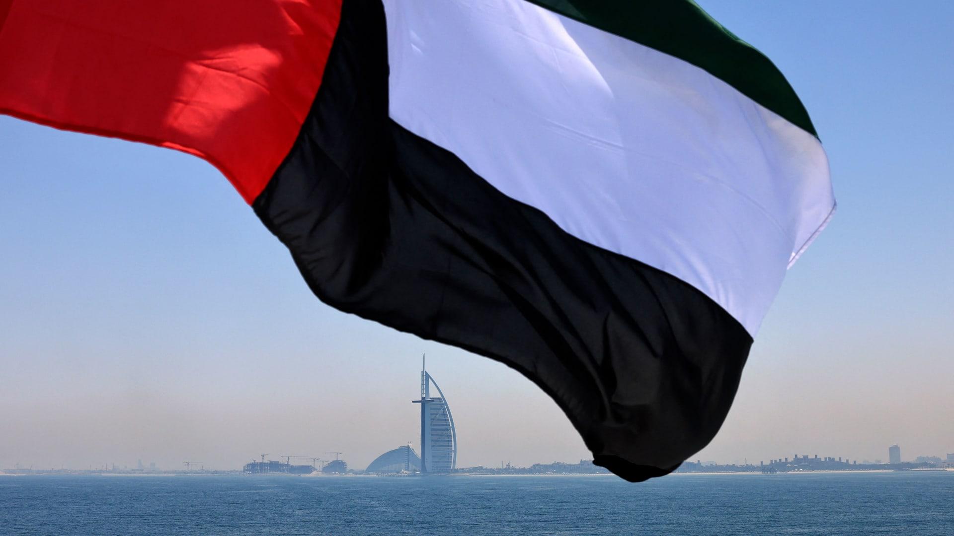 علم الإمارات يرفرف فوق مرسى دبي مع فندق برج العرب في الخلفية