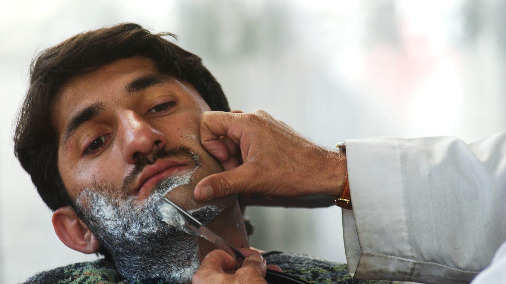 رجل أفغاني يحلق لحيته في محل حلاقة في كابول، أفغانستان - 4 مارس 2003