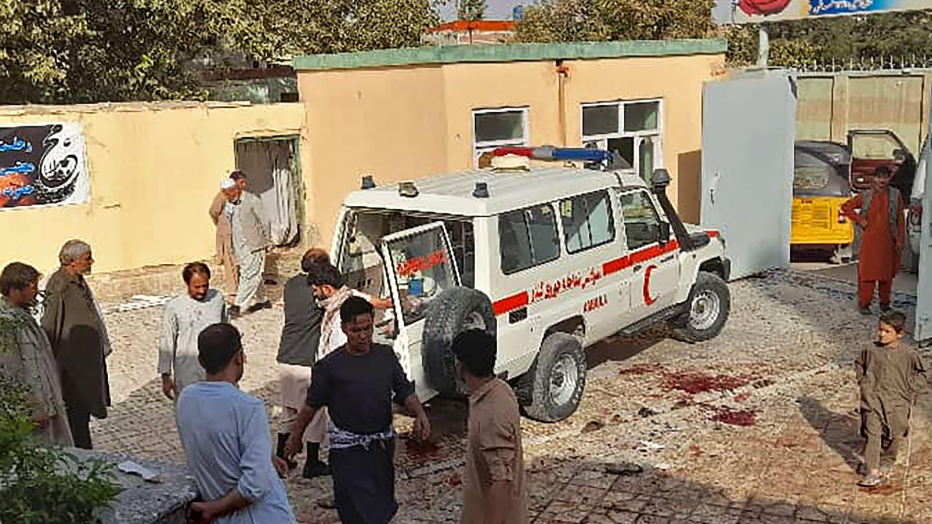 رجال أفغان يقفون بجوار سيارة إسعاف بعد هجوم بقنبلة على مسجد في قندوز، في 8 أكتوبر 2021