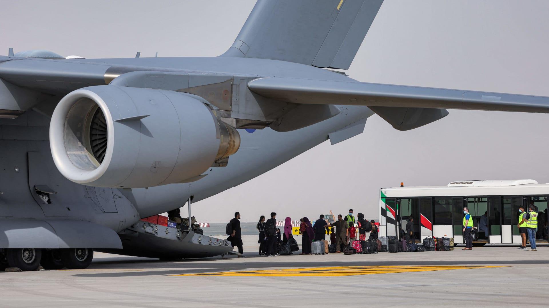نزول أشخاص من طائرة نقل عسكرية تابعة للقوات الجوية الملكية من طراز بوينج C-17A Globemaster III تحمل أشخاص تم إجلاؤهم من أفغانستان وتصل إلى مطار آل مكتوم الدولي في الإمارات العربية المتحدة في 19 أغسطس 2021.