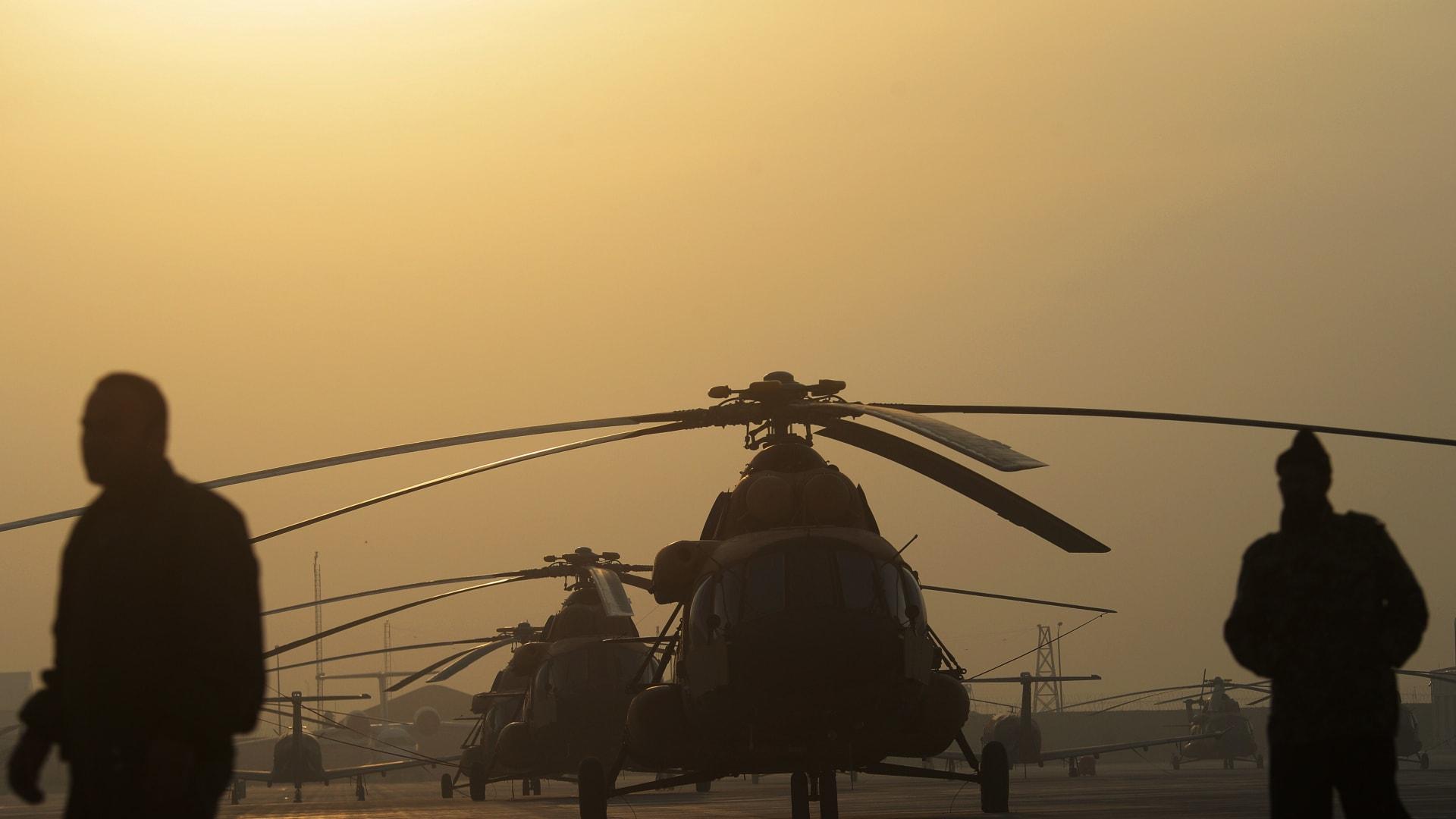 جنود من الجيش الوطني الأفغاني يسيرون بالقرب من طائرات هليكوبتر في مطار كابول الدولي في 24 فبراير 2014.